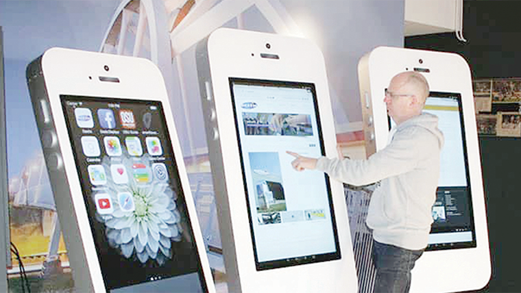 A man tries out a giant iTab smartphone during a trade exhibition