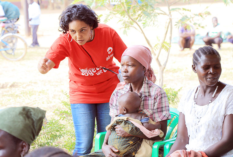 A volunteer guides locals at Kasambya grounds in Kamuli district during a regional health camp