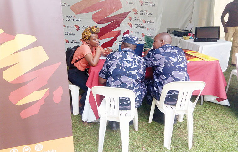 An official guides policemen on how to register a unit trust during a conclusion of the Capital Markets Week at  Constitution Square on May 10
