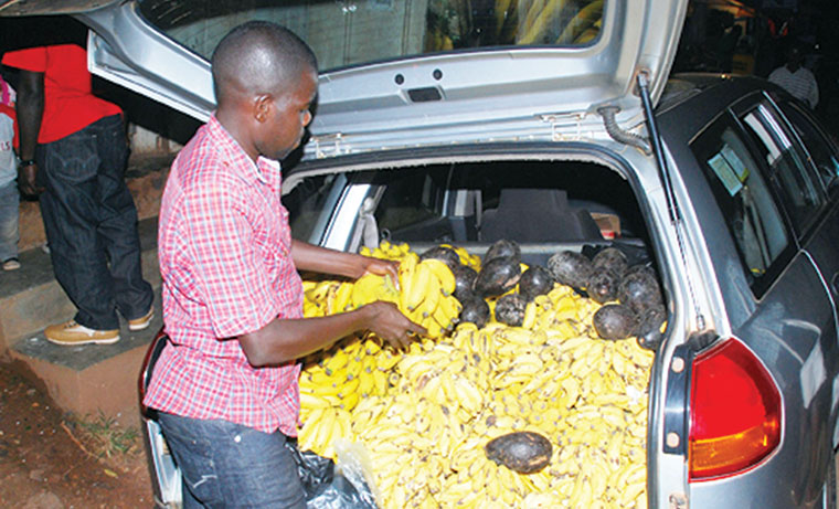 A fruits vendor using his car to supply to customers