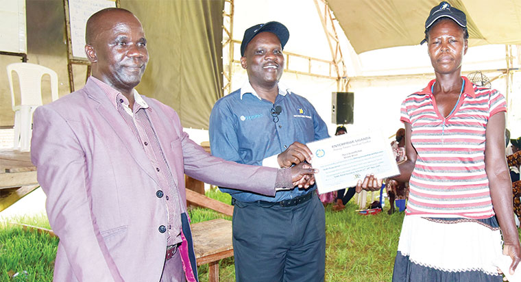 Nusaf's Charles Muswa (L) and Enterprise Uganda ED Charles Ocici (C) hand over a certificate to one of the participants
