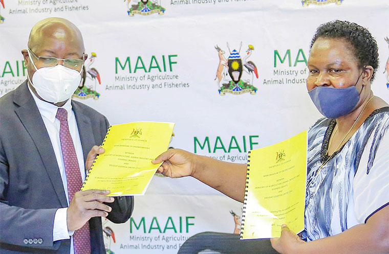 Pius Wakabi Kasajja (L), the ministry of Agriculture permanent secretary, exchanges the MOU with Dr Omalla