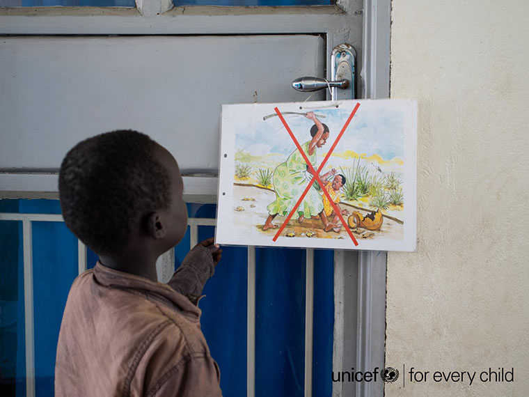 A child looking at a poster against corporal punishment