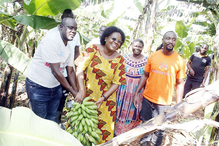 KCCA executive director Dorothy Kisaka (C) with her matoke gift from the Kyabazinga (R)