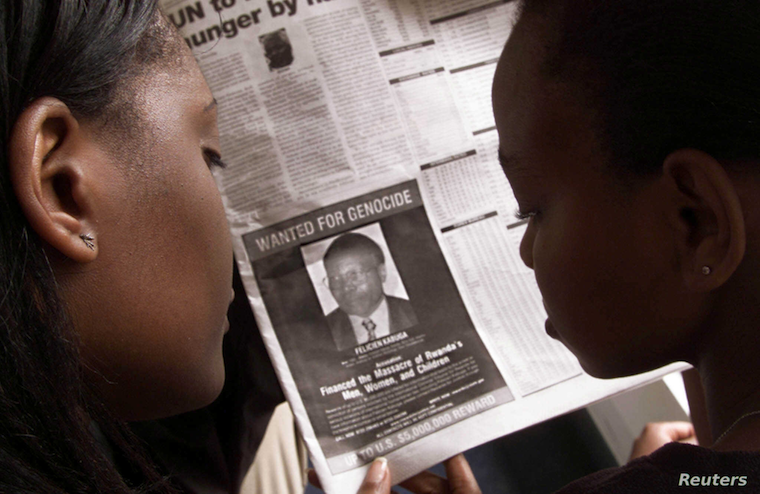 FILE - Women look at a newspaper June 12, 2002, in Nairobi, Kenya, featuring a photo of Rwandan businessman Felicien Kabuga, wanted in connection with Rwanda's 1994 genocide