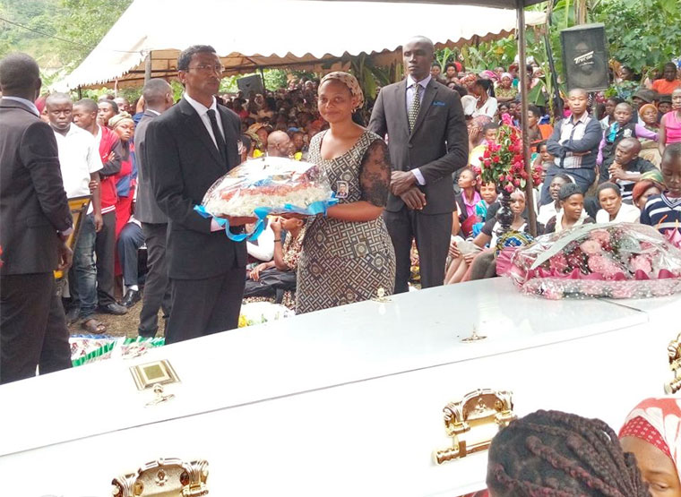 Barry Faure and his sister Maryline Faure lay a wreath on Roy Faure's casket
