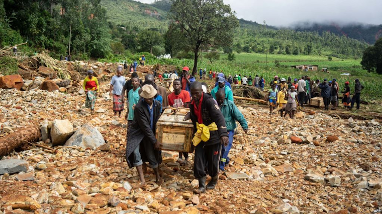 Men carry a coffin on along a makeshift path on the river in Ngangu township Chimanimani, Manicaland province, eastern Zimbabwe, after the area was hit by Cyclone Idai