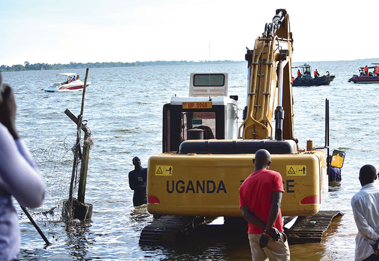 Police excavator trying to pull the wreckage of the sunken boat