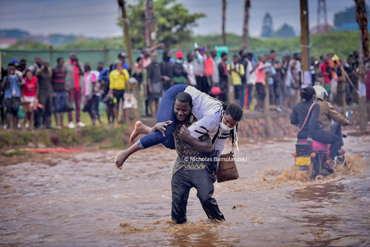 A woman being carried across a flooded road near Clock Tower