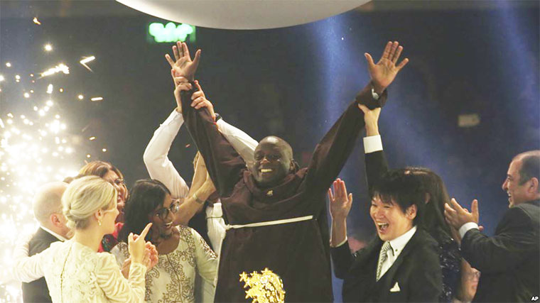 Kenyan teacher Peter Tabichi, center, reacts after winning the $1 million Global Teacher Prize in Dubai, United Arab Emirates, Sunday, March 24
