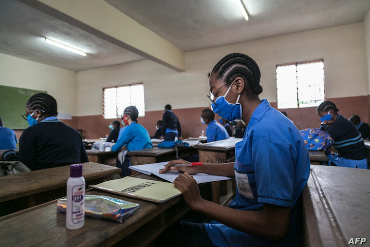 Students wear face masks as a preventive measure against the spread of the COVID-19 coronavirus in their classroom at the Jean Benoit College in Yaoundé, Cameroon