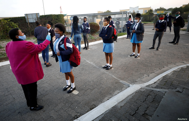 A teacher screens students as schools begin to reopen after the coronavirus disease (COVID-19) lockdown in Cape Town, South Africa