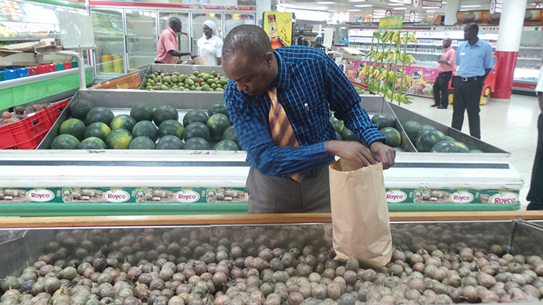 A shopper using a paper bag at a supermarket in Kampala