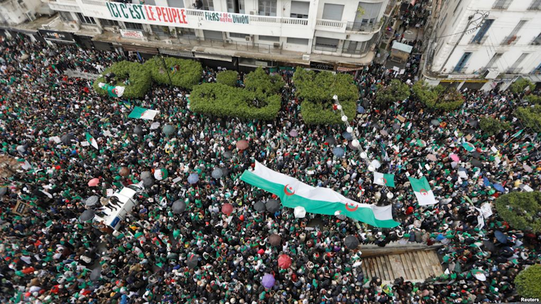 Demonstrators carry Algerian national flags during a protest calling on President Abdelaziz Bouteflika to quit, in Algiers, Algeria