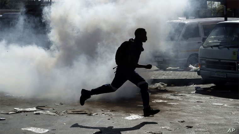 A man runs away from tear gas after making off with goods from a store in Germiston, east of Johannesburg, South Africa, September 3