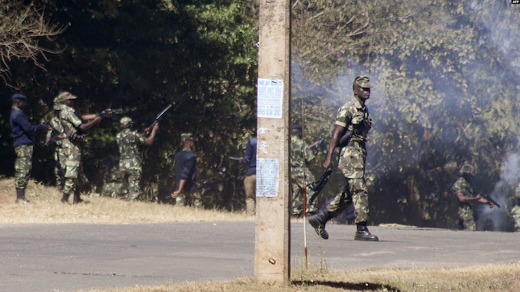 Armed Malawian policemen walk through a cloud of teargas to disperse supporters of The Malawi Congress Party (MCP) in Lilongwe