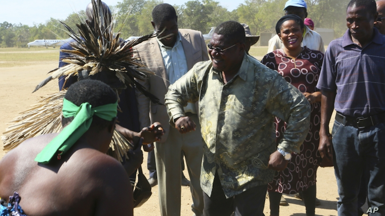 Renamo leader Ossufo Momade, center, performs a dance with locals
