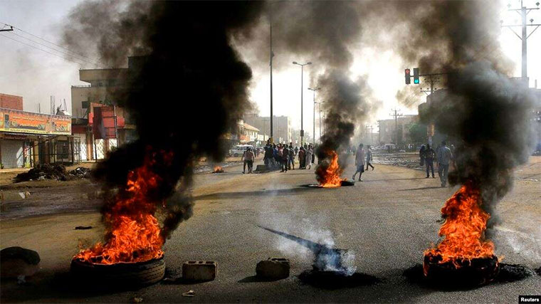 Sudanese protesters use burning tires to erect a barricade on a street, demanding that the country's Transitional Military Council hand over power to civilians, in Khartoum