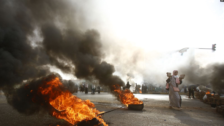 A Sudanese protester walks past burning tires as military forces tried to disperse the sit-in outside Khartoum's army headquarters on June 3