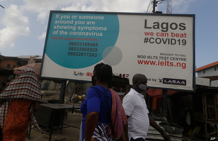 FILE People walk past a sign advising residents to report if they have coronavirus symptoms, in Lagos, Nigeria