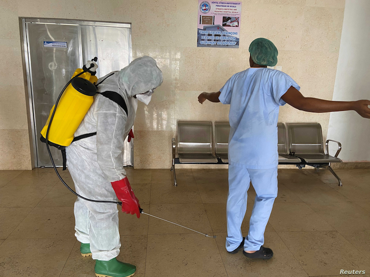 A health worker in Cameroon getting disinfected