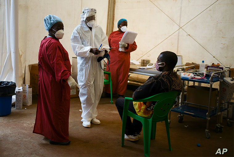 FILE - A COVID-19 patient, right, is seen to by health workers at Queen Elizabeth Central Hospital in Blantyre, Malawi