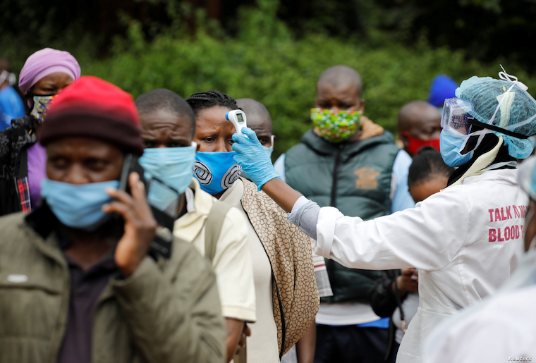 FILE - A health worker takes the temperature of a person standing in line for mass testing in an effort to stop the spread of the coronavirus disease (COVID-19) in the Kibera slum of Nairobi