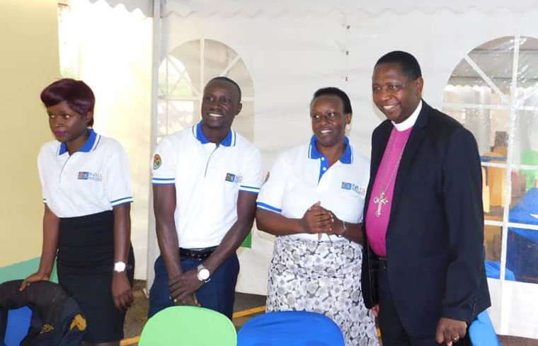 Archbishop Stanley Ntagali with NMS staff