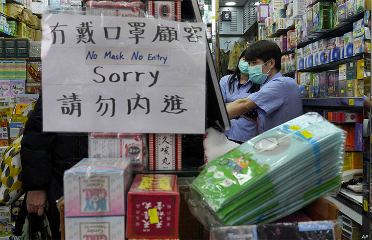 A notice announces no entry to customers without protective face masks at a pharmacy in Hong Kong, Feb. 10, 2020