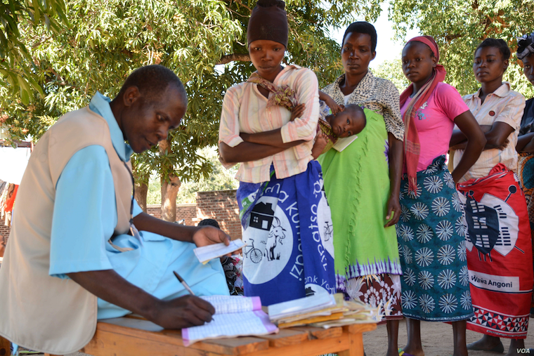 Malawi health workers taking records of patients