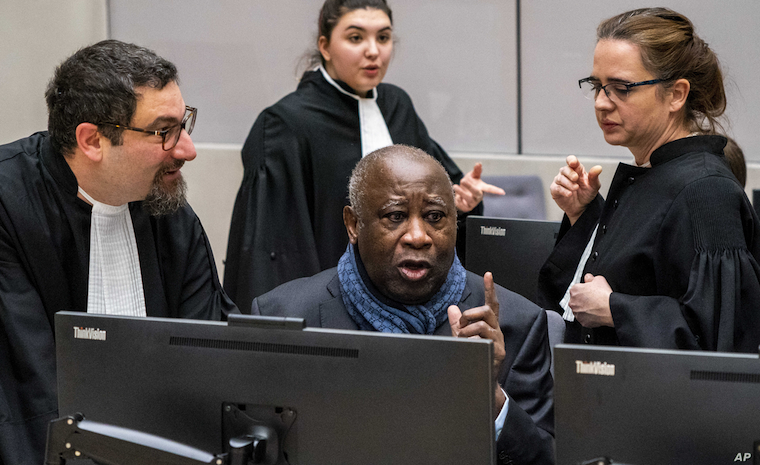 Former Ivory Coast president Laurent Gbagbo talks to his legal team at the International Criminal Court in The Hague, Netherlands earlier in February