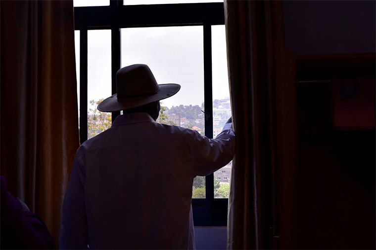 President Museveni looking through the window at State House