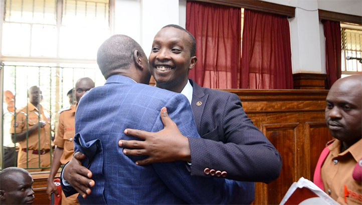 Aaron Baguma embraced by a family member after the DPP dropped murder charges against him