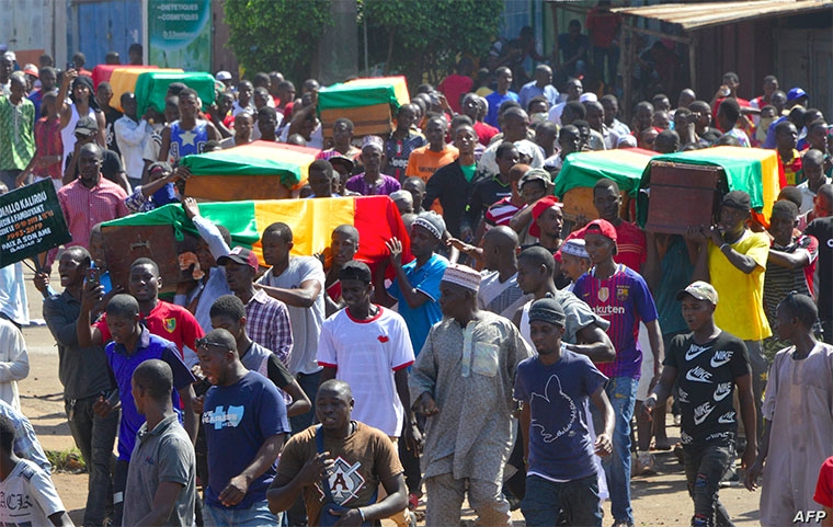 People carry coffins during the funeral after street protests and unrest that resulted in nine deaths in Conakry, on Nov. 4, 2019