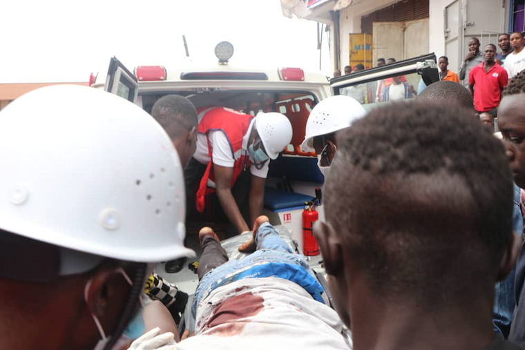Uganda Red Cross Society personnel helping one of the injured victims in Kisenyi