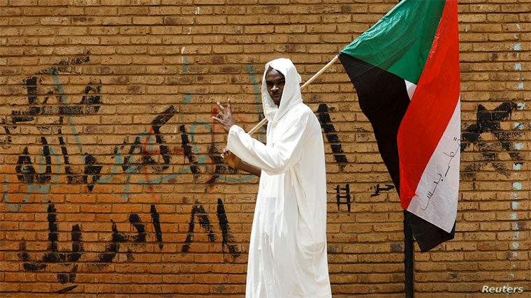 FILE - A protester makes a victory sign as he carries a Sudanese flag in front of the Defense Ministry in Khartoum, Sudan, April 19, 2019