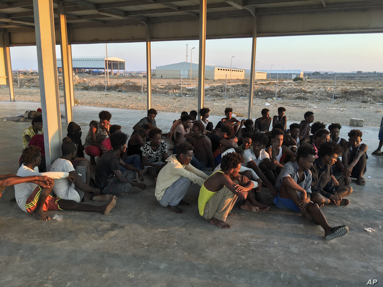 Rescued migrants sit on a coast about 100 kilometers (60 miles) east of Tripoli, Libya, July 25, 2019