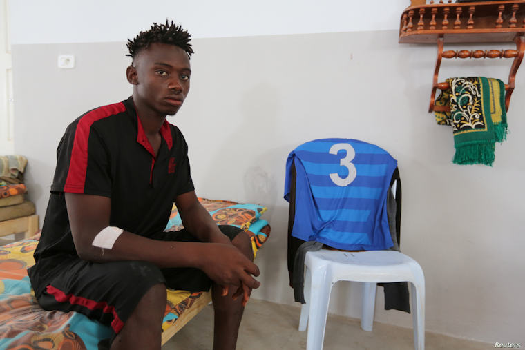 An African migrant who a government source said was rescued after the boat he was traveling in capsized in the Mediterranean Sea off the Tunisian coast, sits inside a local Red Crescent chapter in Zarzis, Tunisia, July 4, 2019