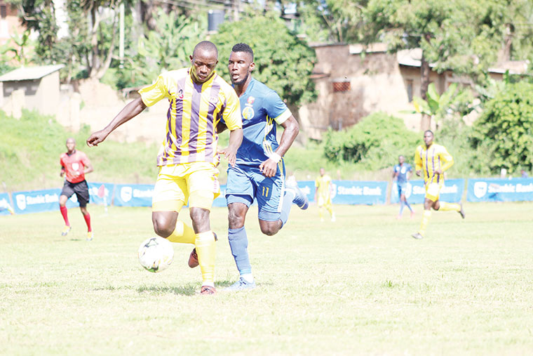 Proline's Musitafa Mujuzi (L) shields the ball from Bright Stars' Nelson Ssenkatuka during the Uganda Cup final in May