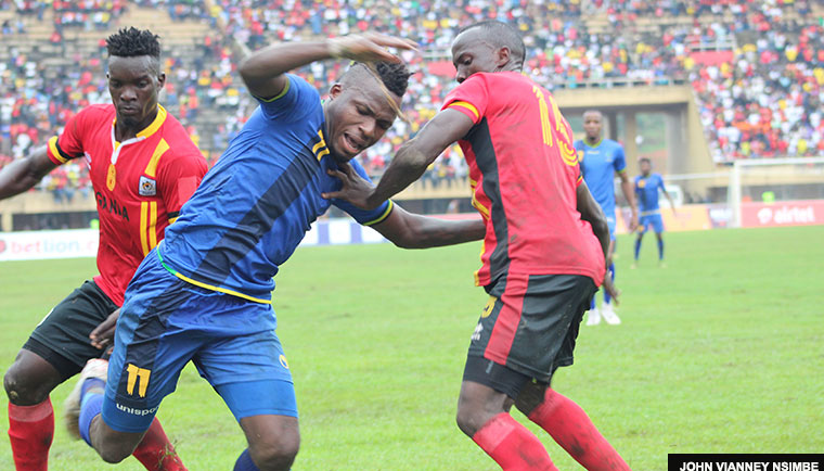 Tanzania forward Thomas Ulimwengu is tackled by Cranes left-back Godfrey Walusimbi and midfielder Khalid Aucho