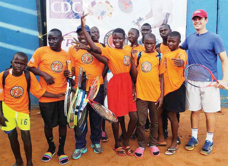 US Mission public relations o cer Phil Dimon (far right) stands in front of the Arthur Ashe banner alongside some of the young tennis players discovered during the embassy's tennis development programme