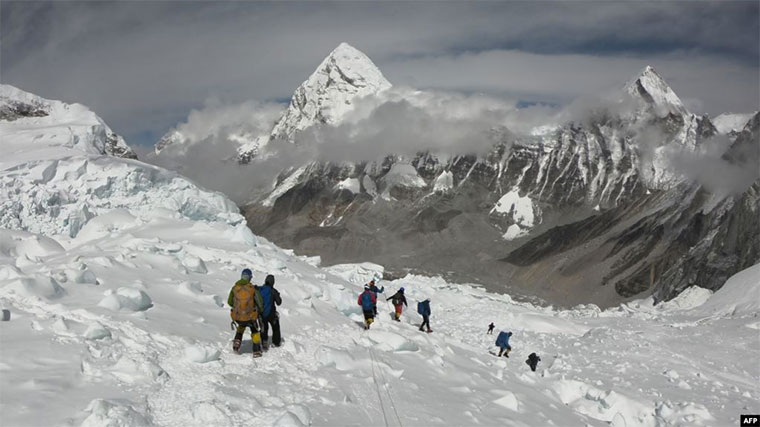 FILE - Mountaineers walk near Camp One of Mount Everest, April 29, 2018, as they prepare to ascend on the south face from Nepal