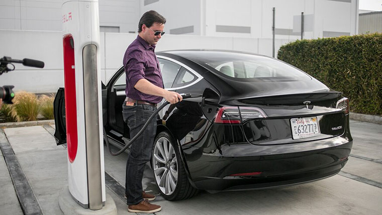 A man charges the battery of a Tesla Sedan at a supercharger station. Fuel stations could soon be replaced with charging centres for non-fuel cars