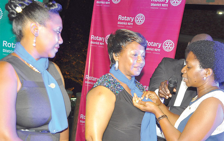 Rotarian Dorcas Tusubira (R) initiates new female members to the club recently